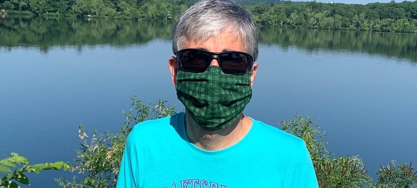 Person standing in front of lake with mask on