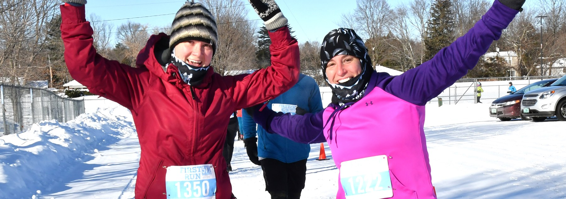 Ladies with arms up running in the winter