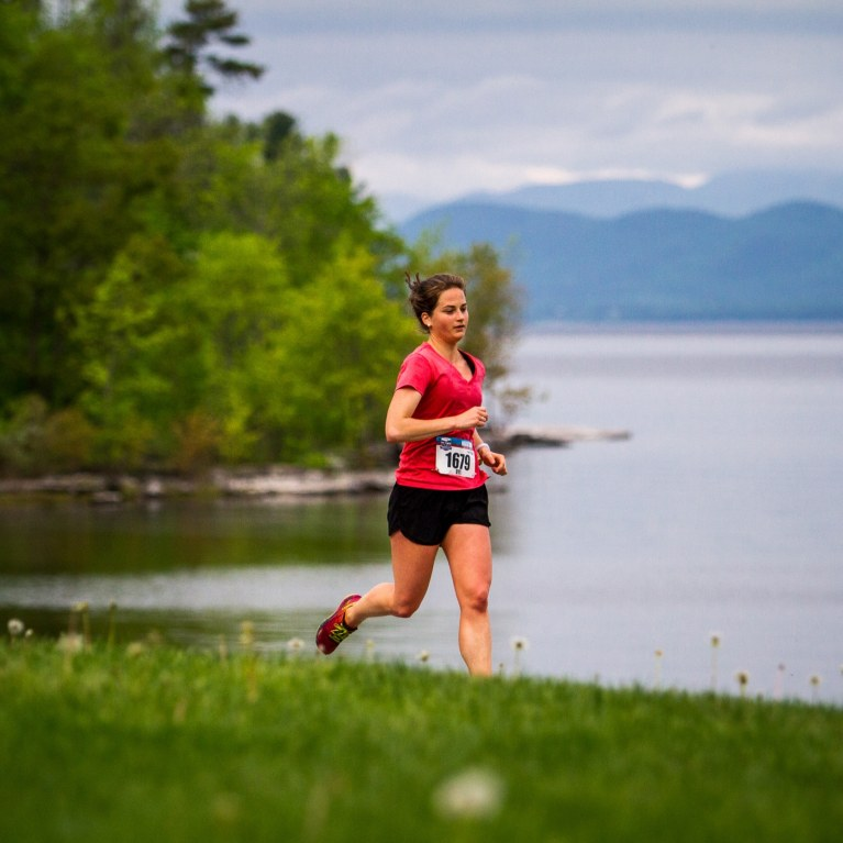 woman running on bike path in front of lake