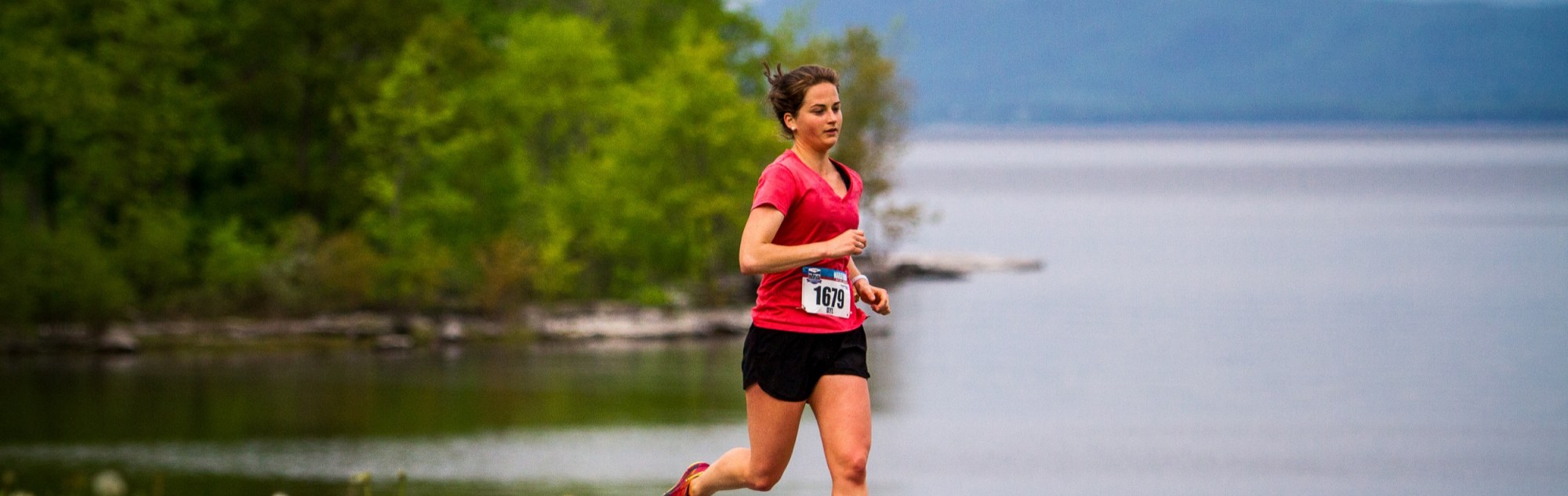 woman running in front of lake