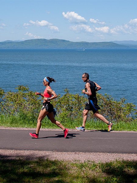 Runners running along lake Champlain